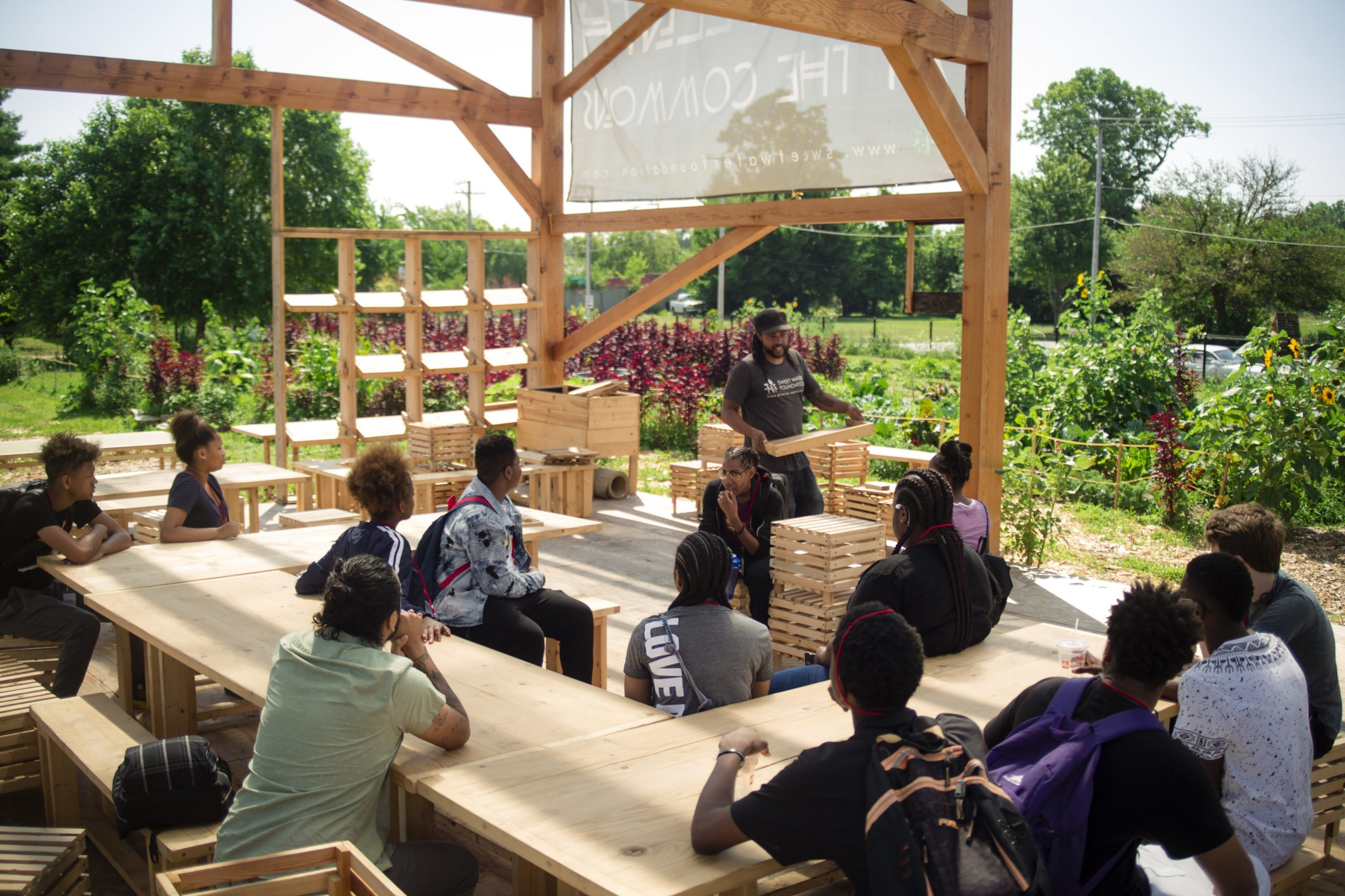 Youth gather in an open-air barn surrounded by green space