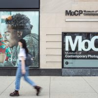 Pedestrians walk past a building with a sign on its facade that reads MoCP, Museum of Contemporary Photography