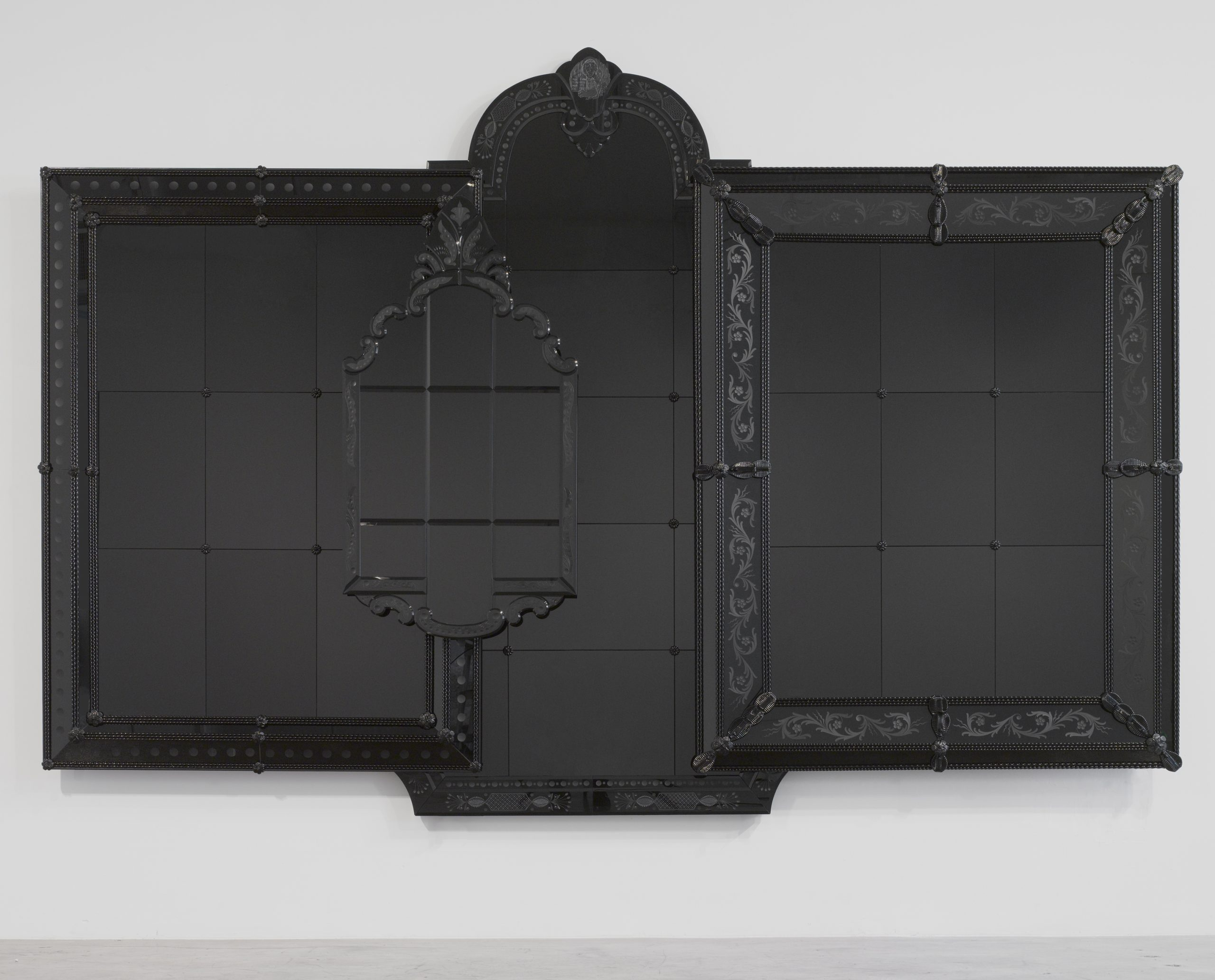 A black and reflective artwork made from the composite of four ornate frames.