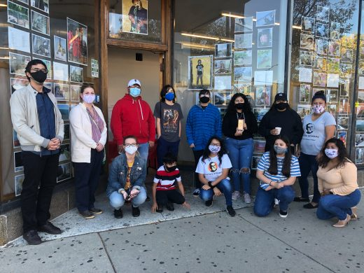 A group of people wearing face masks stand in front of a storefront with photographs in the window.