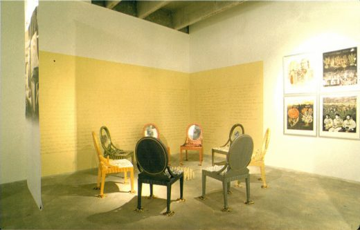 Panorama of an art installation: seven rounded-back chairs circle at center, a hanging banner to the left, a golden wall with text in the background and four framed artworks to the right.