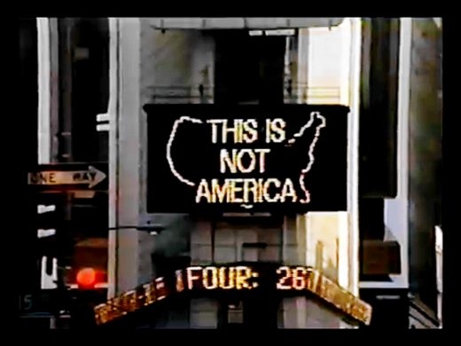 """Photograph of lighted billboard with """"This is not America"""" text on the shape of the continental United States."""