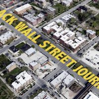 In an aerial image of a Chicago neighborhood, Black Wall Street Journey is digitally painted along a street in yellow capital letters