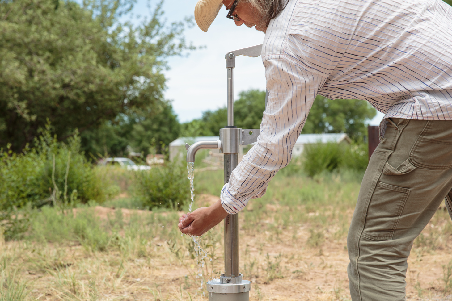 A person pumps water from a stainless-steel pump.