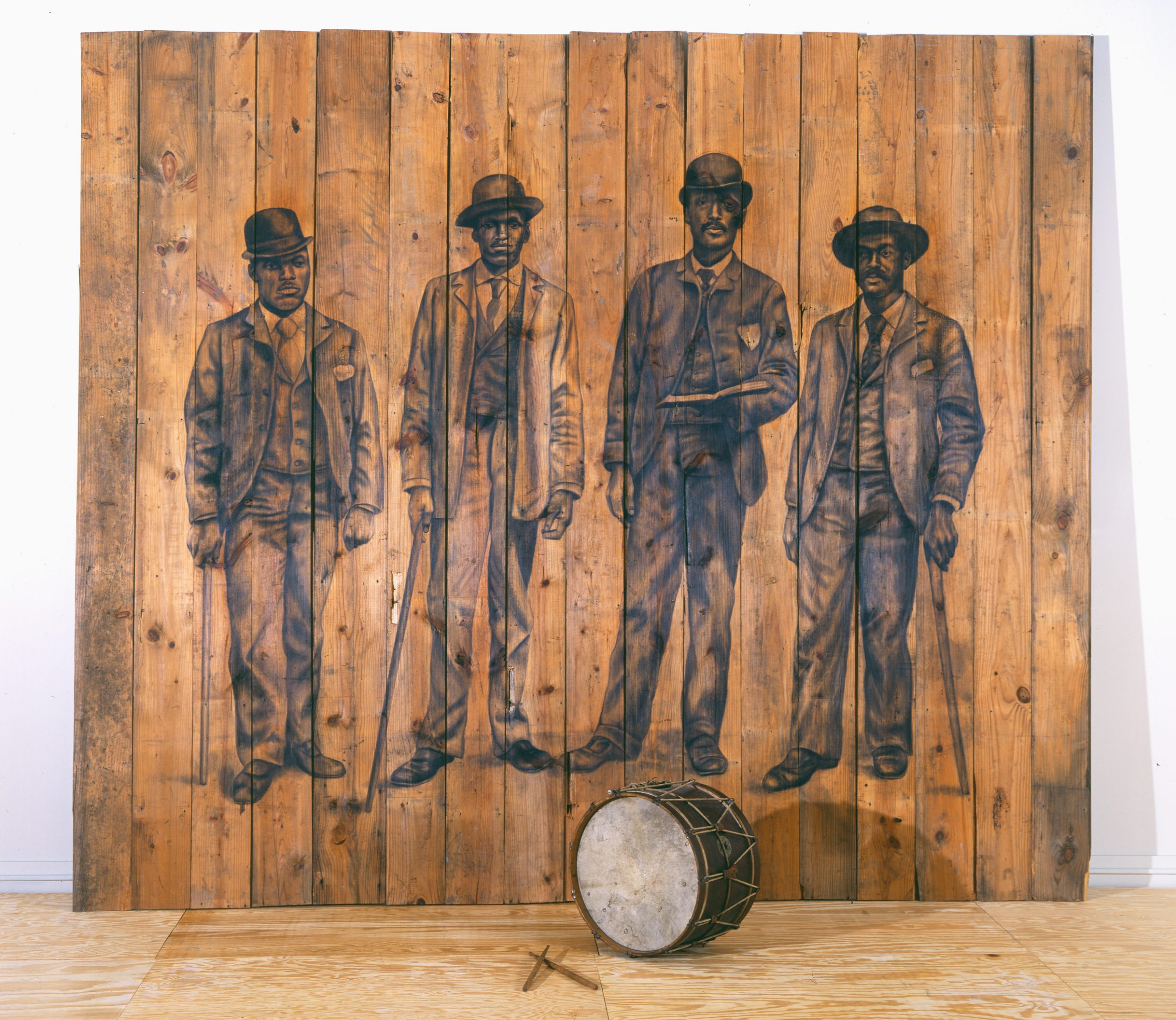 Charcoal drawing of four besuited Black men on a wooden panel with an old drum and drumsticks.