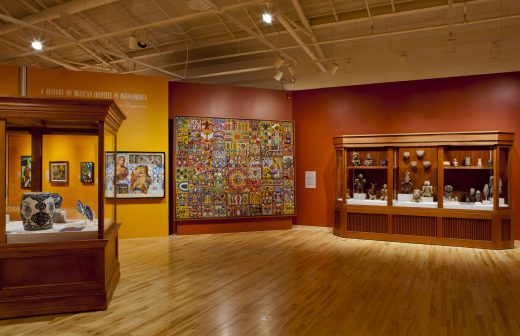 A museum gallery showcasing Mesoamerican pottery, paintings and tapestries against a red wall.