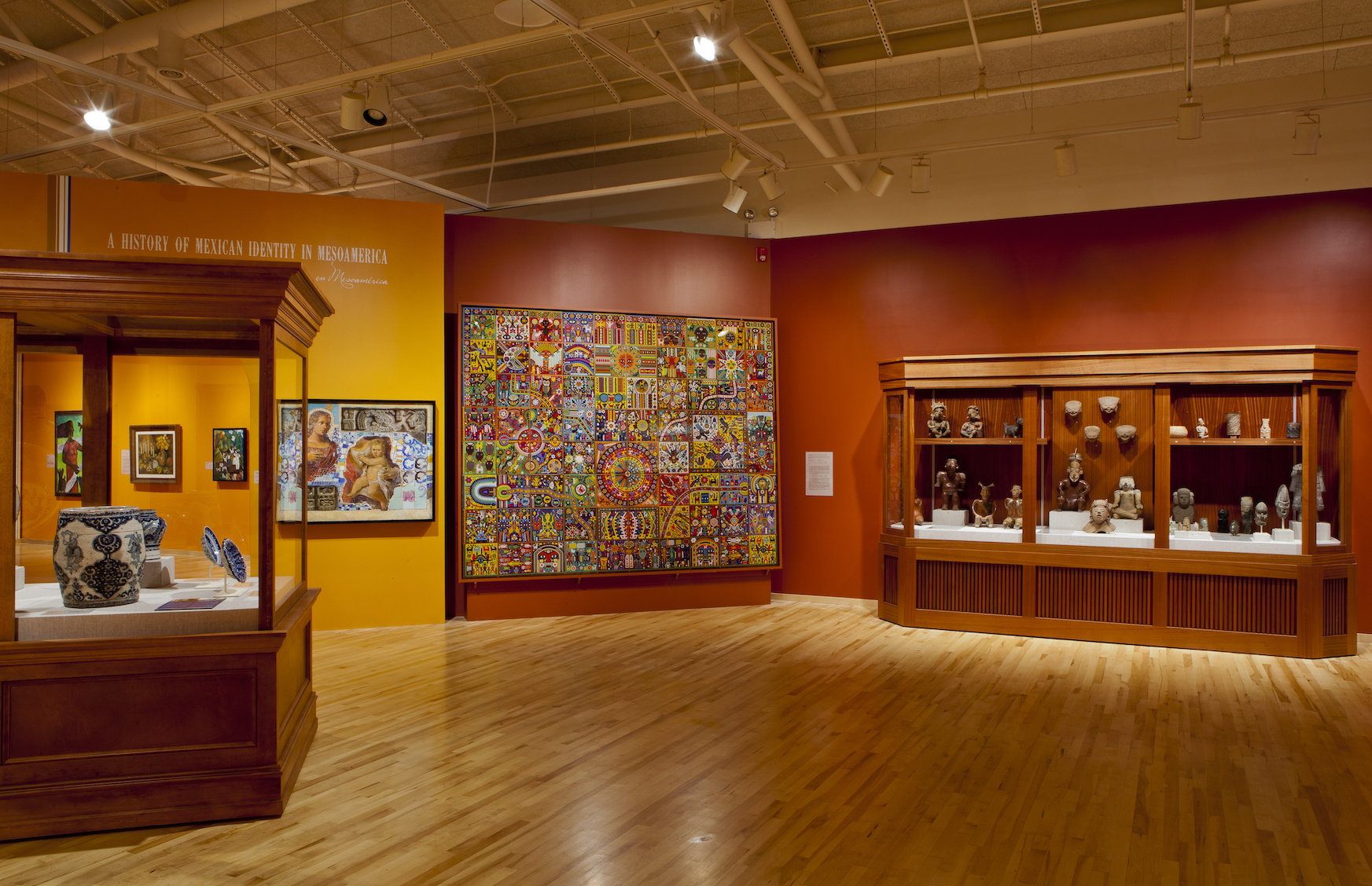 Alt: A museum gallery showcasing Mesoamerican pottery, paintings and tapestries against a red wall.