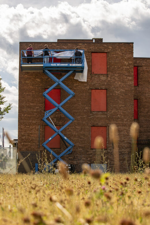 Three people on a scissor lift drape a banner in front of a brick building