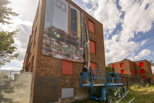 Three people on a scissor lift unfurl a banner in front of a brick building