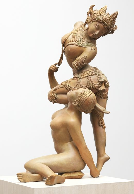 A heavily patinated bronze sculpture depicting two intertwined female figures
