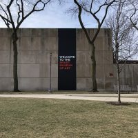 Exterior of the museum with a black banner that reads Welcome to the Smart Museum of Art
