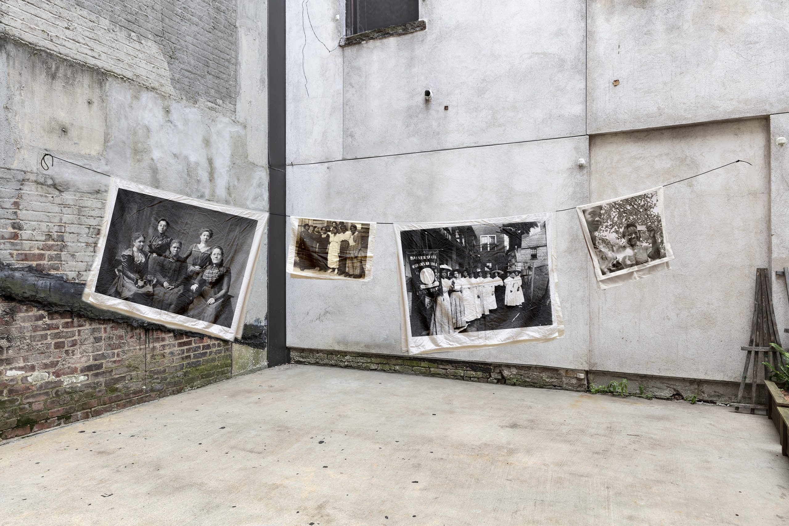 Four photographs of women printed on linen hang on a clothesline in an empty lot
