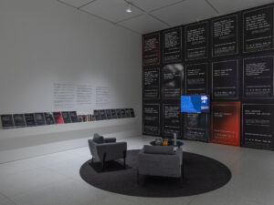 Gallery installation showing a TV monitor on a wall covered with posters and a pair of chairs