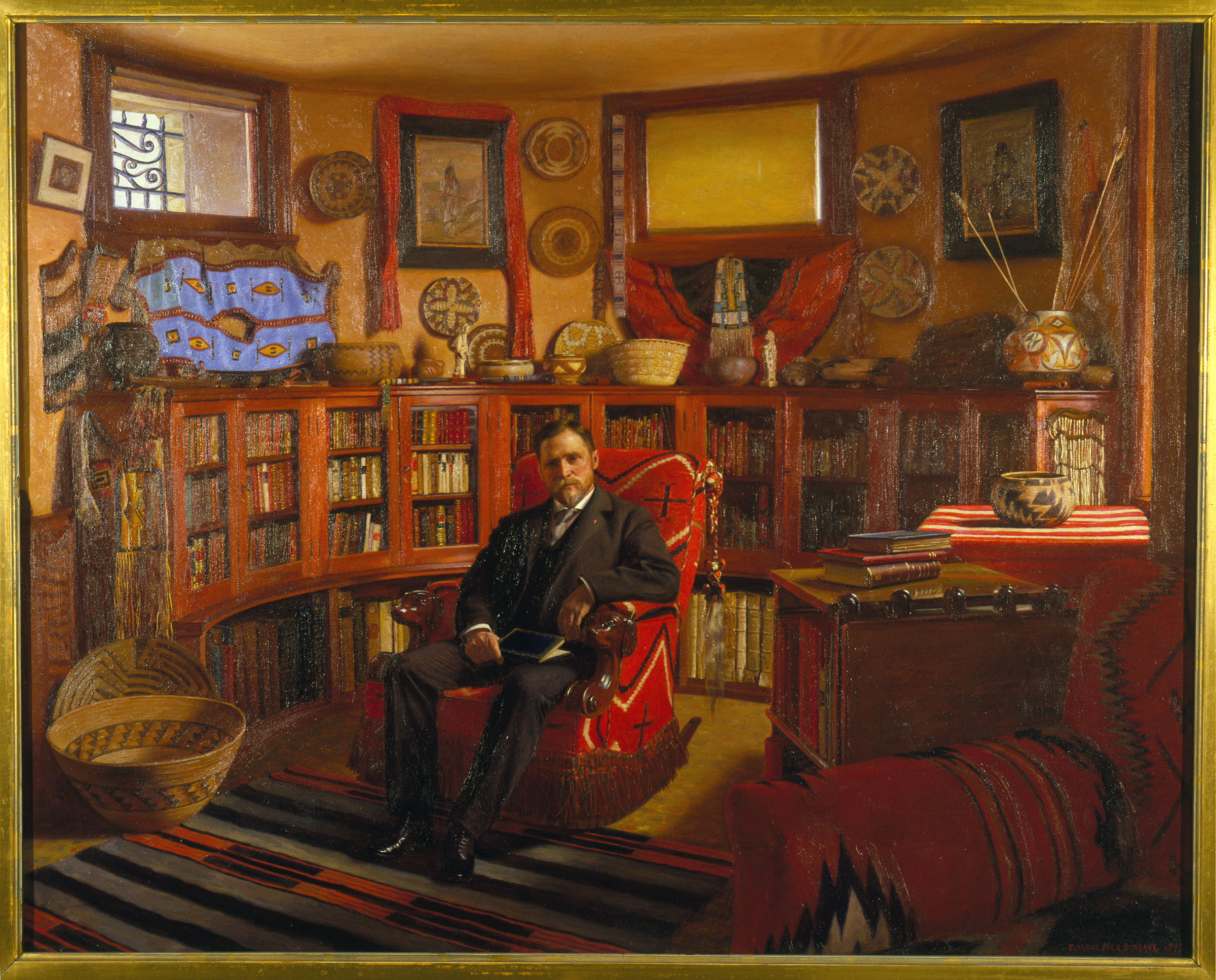 A painted portrait of a man seated in a study filled with books and Native American artifacts.