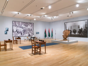 Gallery installation consisting of school desks, a woven throne, flags, and large scale photographs.