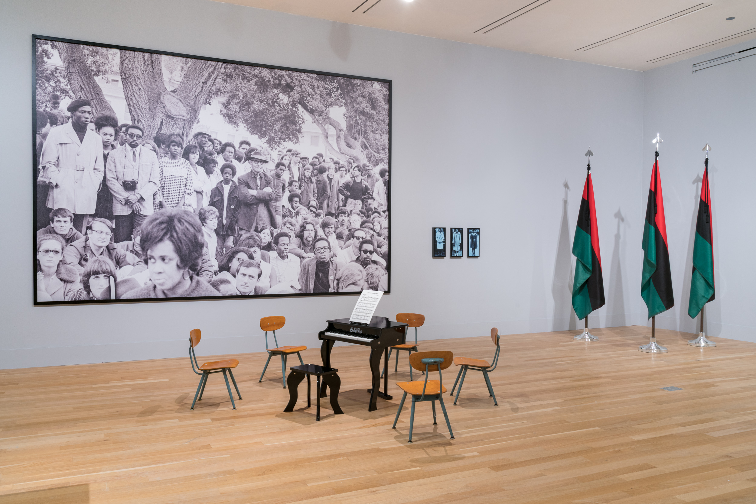 Gallery installation with a small piano, three flags, and a large scale photograph.