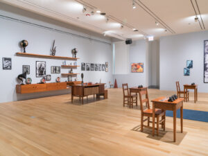 Gallery installation with school desks, photographs, and a collection of items related to the Black Panthers.