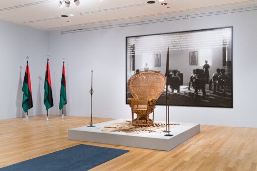 Gallery installation featuring a woven throne, three flags, and a large scale photograph of a classroom.