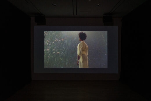 Gallery black box theatre showing a film of a woman standing in a yellow kimono.