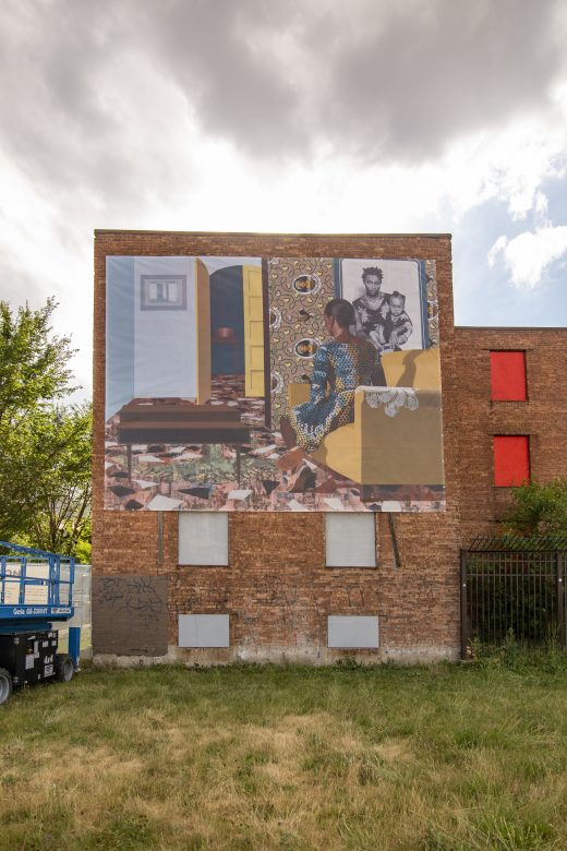 A vinyl mural hangs on the outside wall of a brick building