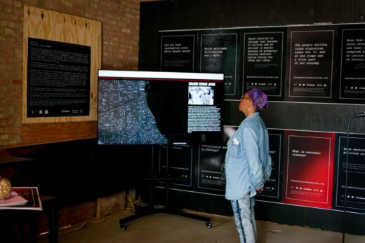A woman in denim watches a TV monitor mounted in from of posters in a gallery exhibition.