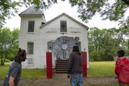 A metal bank vault hangs over the doorway of a church