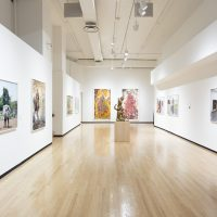 Gallery view with large paintings, photographs and a bronze sculpture in the center of the room