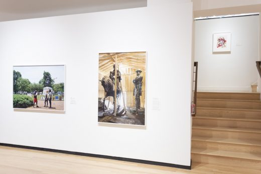 Gallery view with two large scale photographs of monuments and a small drawing up a flight of stairs