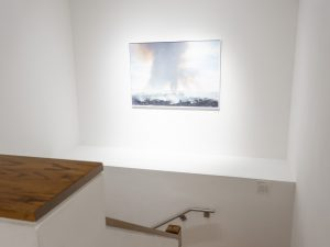 Gallery stair case with a large photograph of a burning cane field.