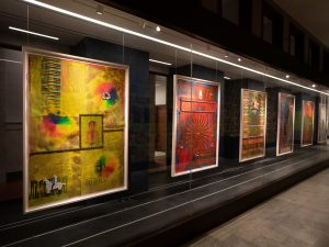 A series of paintings hang behind a glass display case