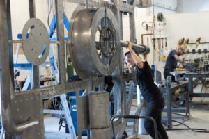 A person hoists a metal rod during the fabrication process of a bank vault
