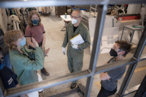 Four people in conversation in a metal fabrication studio