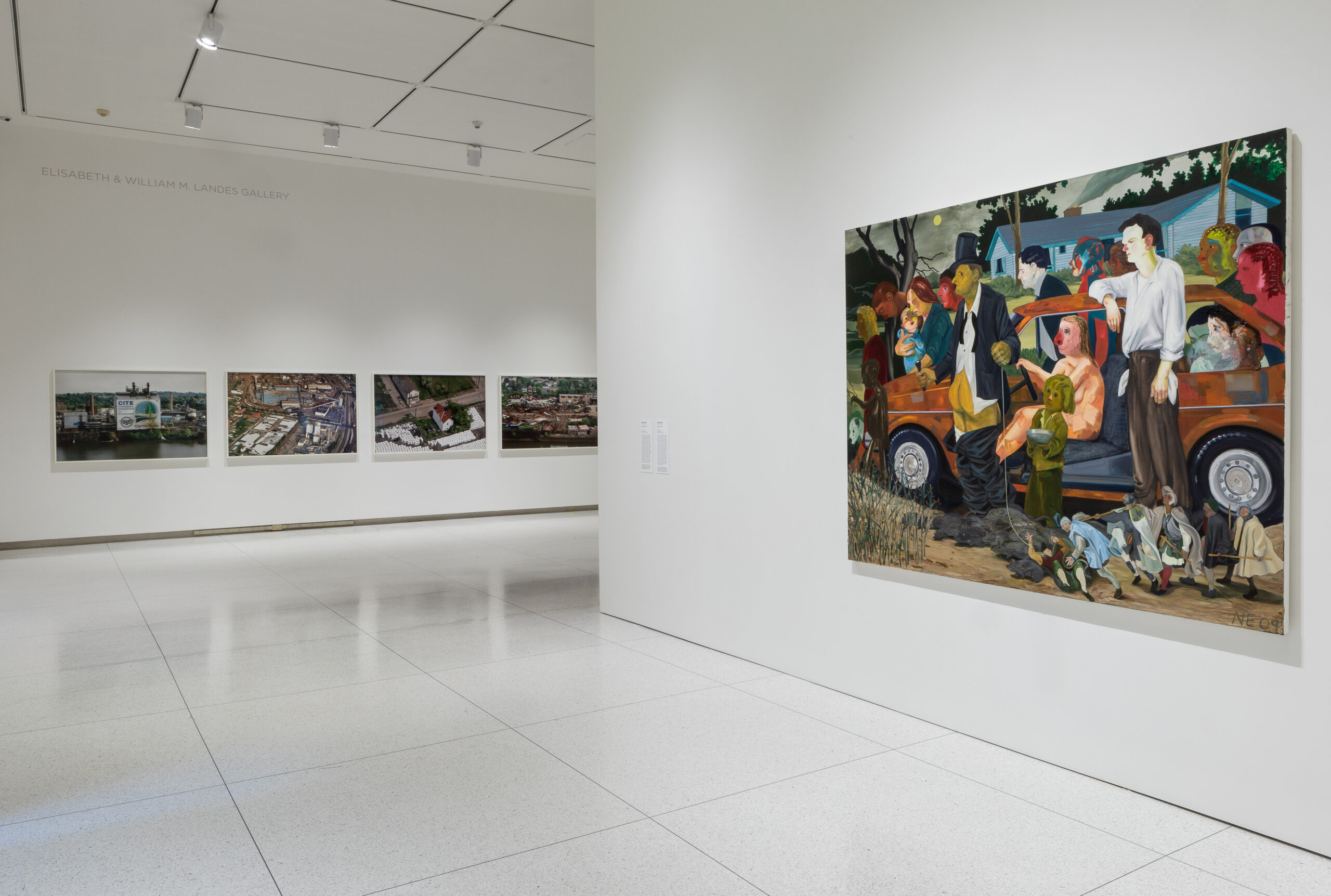 Gallery installation with a vibrant comic painting and aerial photographs.