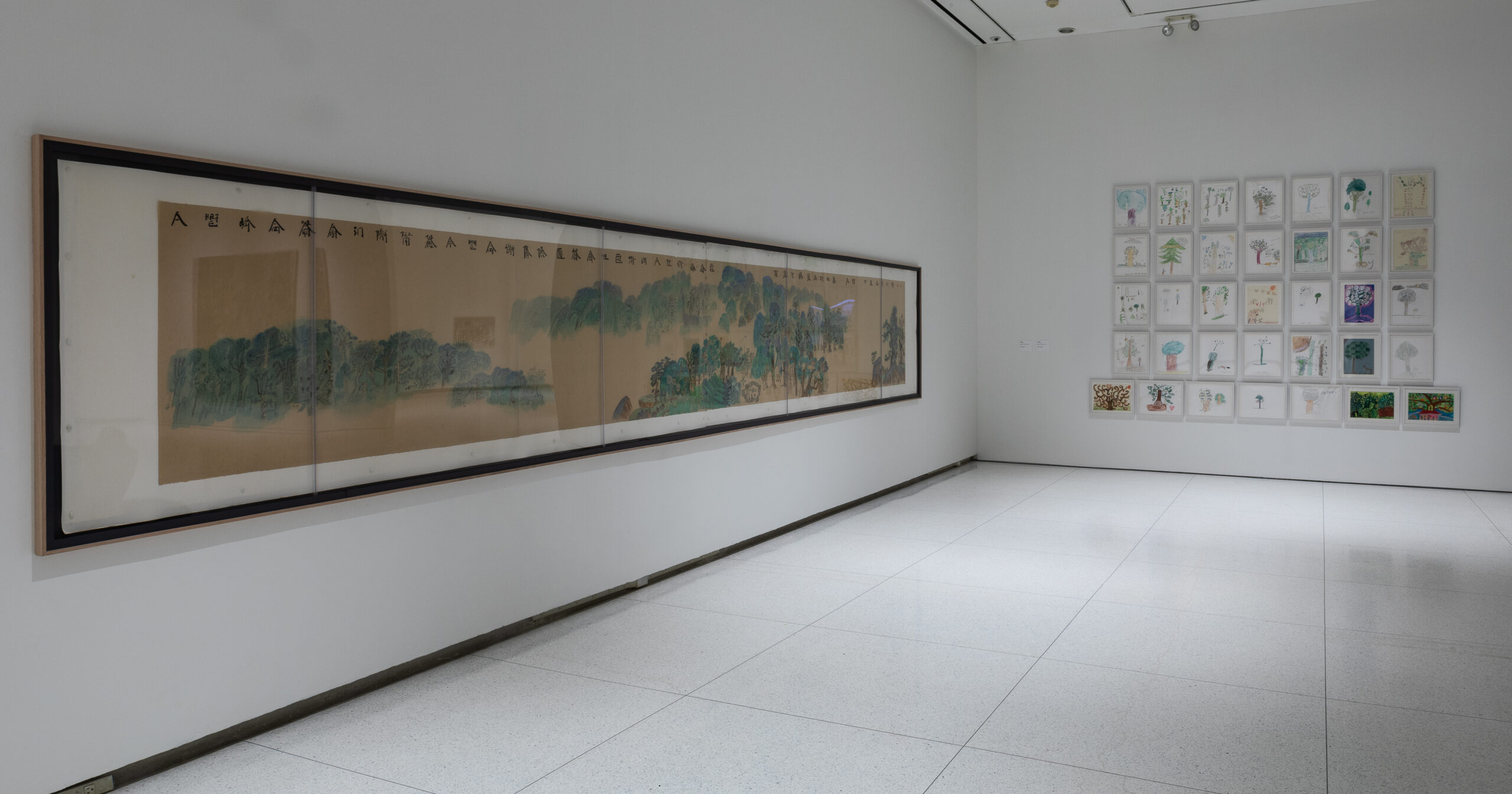 Gallery installation with framed children's drawings and a long scroll landscape painting.