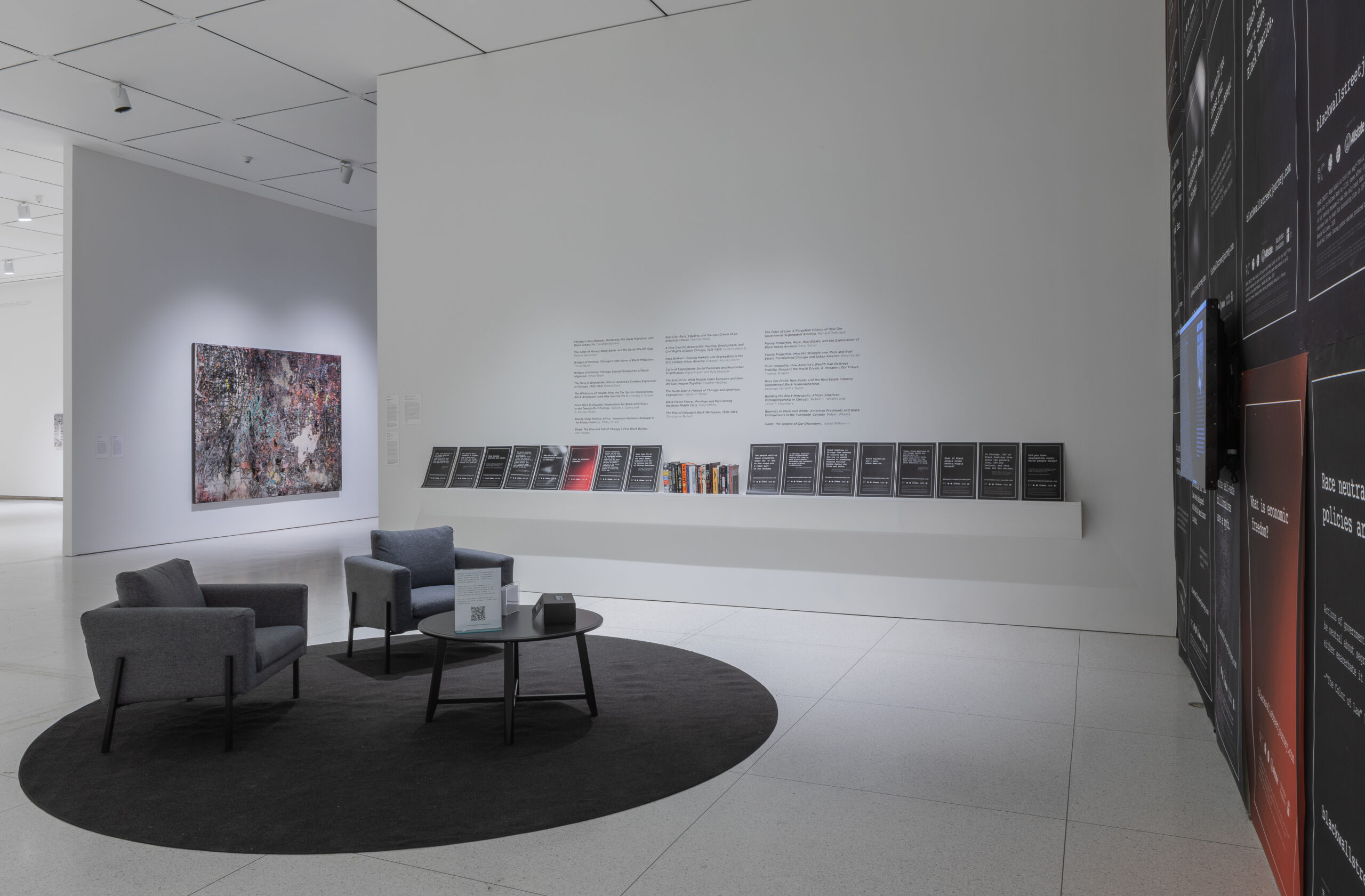 Gallery installation with a seating area, posters, and a large painting in the background.