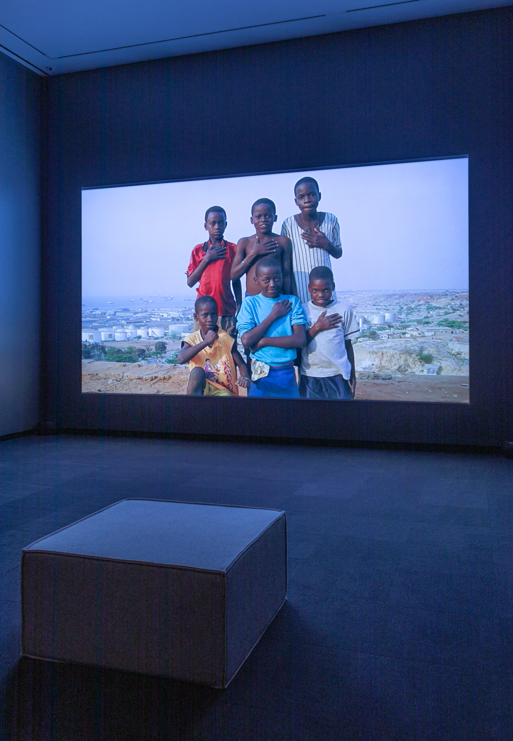 Gallery installation with a video projection of six boys in a black-box theatre.