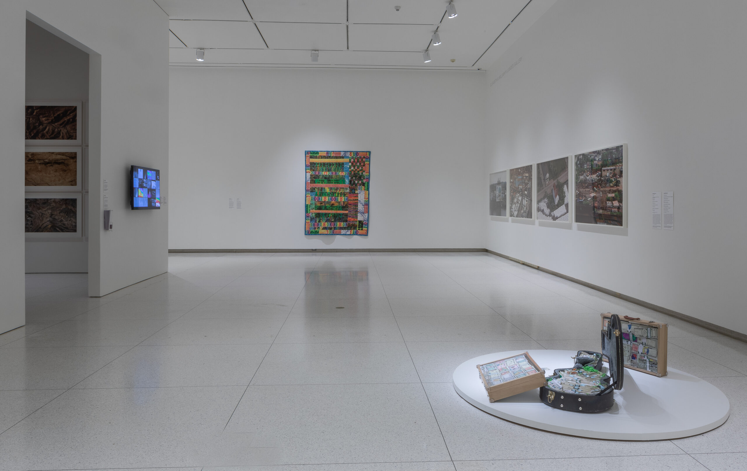 Gallery installation including a colorful tapestry, a video monitor, a guitar case, and photographs.