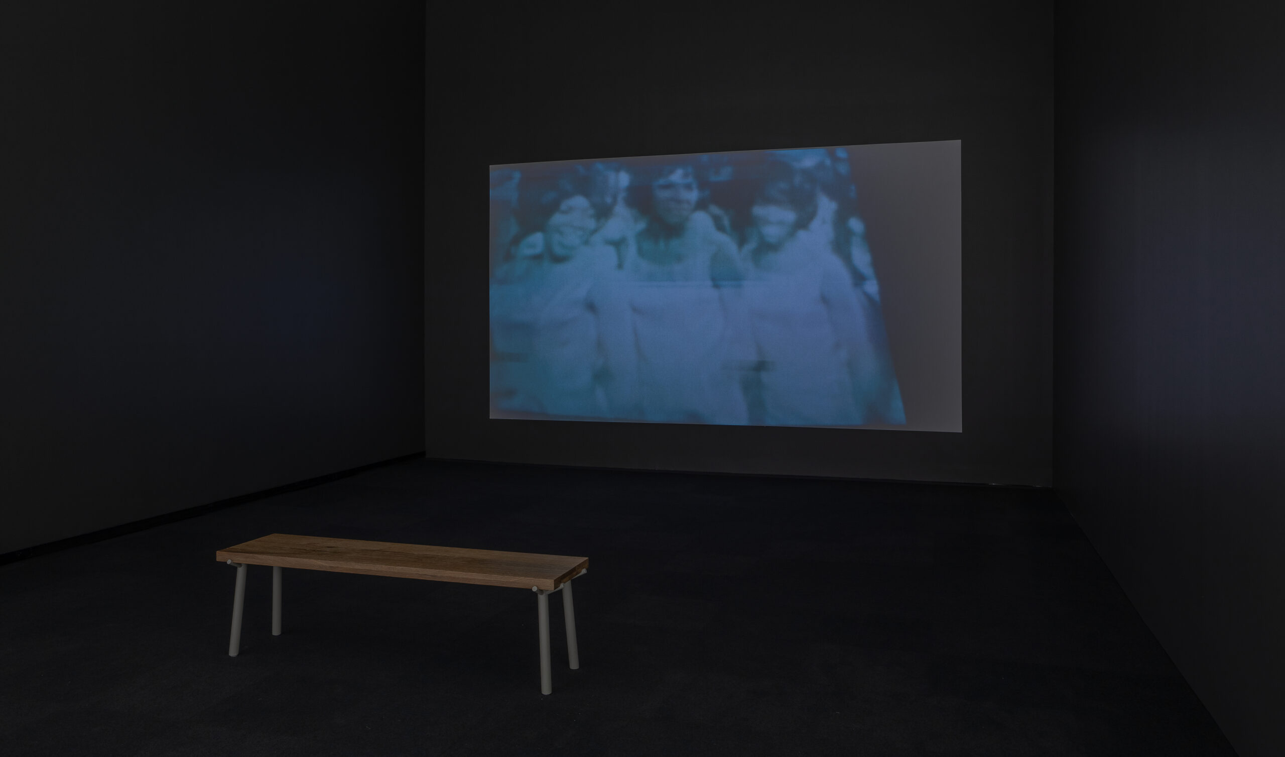 Gallery installation of a dark theatre with a video projection of dancers.