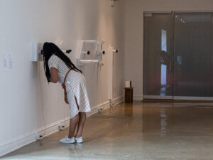 Gallery installation with a person leaning into a wall mounted sculpture.
