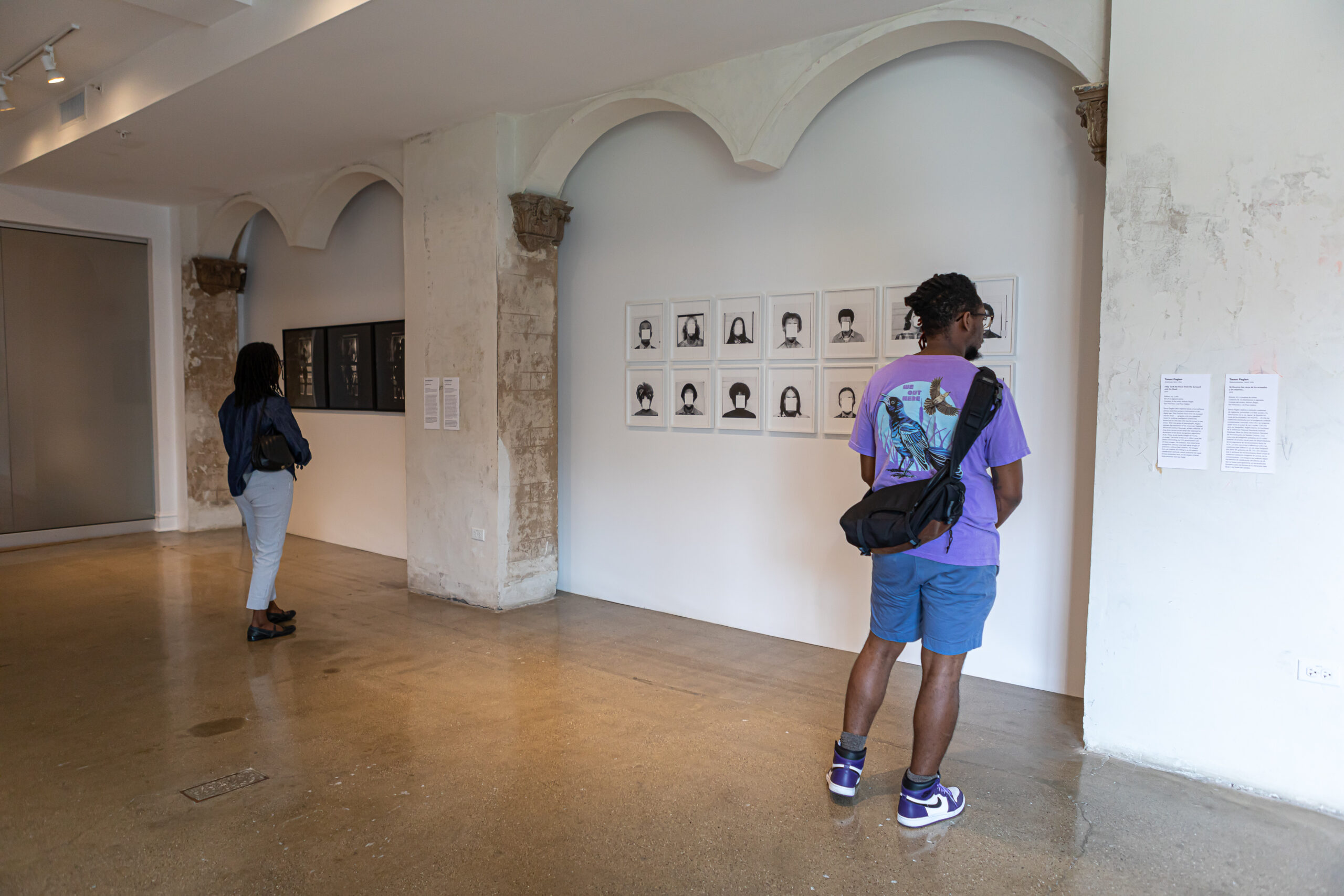 Gallery installation featuring two people gazing at black and white photographs.