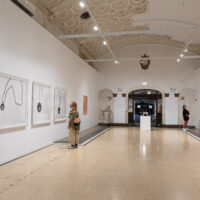 Gallery installation in a long bank corridor featuring a large charcoal on wood panel drawing.