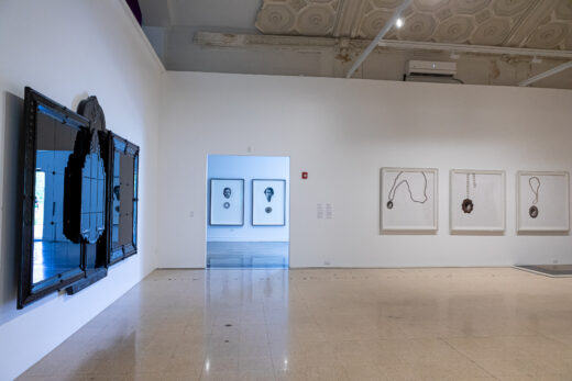 Gallery installation with multiple black and white artworks
