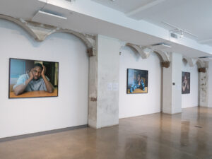 Gallery installation of three large color photographs of individual students seated at desks.