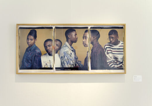 Gallery installation featuring a three-panel photograph of students.