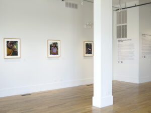 Gallery installation displaying three photographs, each a portrait of a student.