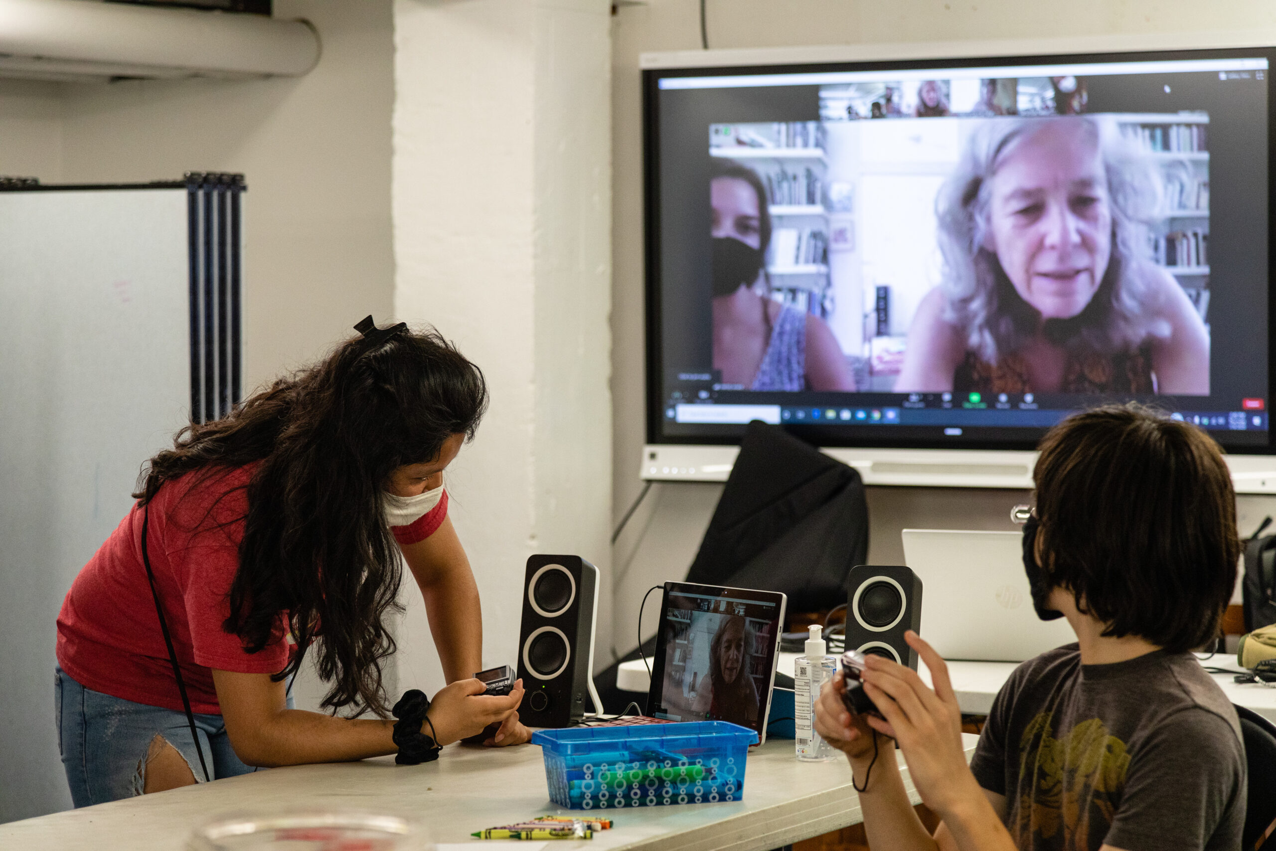 Two youth, wearing masks, work with hand-held cameras while other participate remotely via a wall-mounted monitor