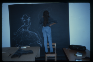 The artist stands on a chair, drawing in chalk on a large piece of black paper