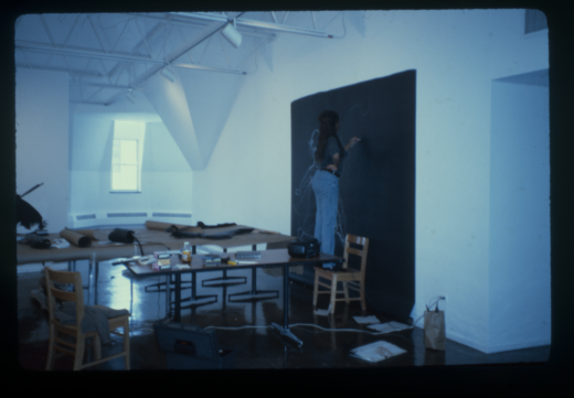 The artist stands on a chair to make a large chalk drawing on black paper