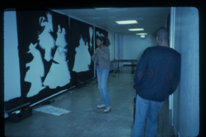 Two people in a gallery hallway, one leans against the wall and one stands laughing