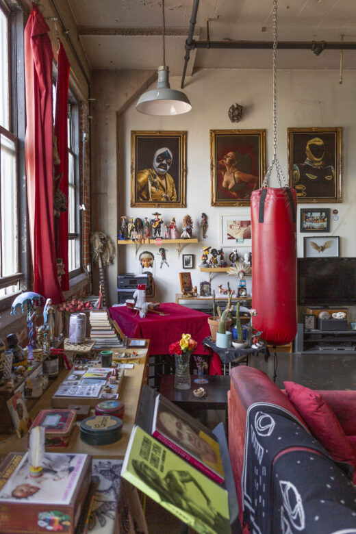 An apartment filled with paintings, personal items, figurines, a punching bag, and ephemera.